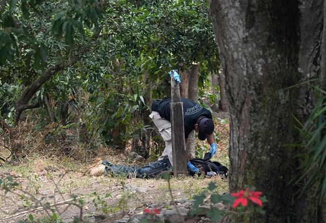 Un agente del equipo de Inspecciones Oculares de la Policía Nacional Civil revisa el cadáver de José Antonio Gómez, alias Güereja, en la mañana del 26 de marzo. El médico forense que reconoció el cuerpo contabilizó 23 orificios de bala. Foto Marvin Recinos (AFP).
